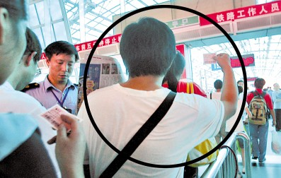 昨日,火车北站,记者(图标处)持票从检票员身旁走过 记者 邹飞 摄