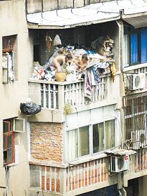 两名小女孩在满是垃圾废品的阳台上嬉闹攀爬