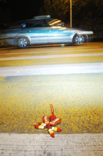 """2009年8月4日,杭州,一只蝴蝶坠饰落在出事的""""爱心""""斑马线上。据目击者称,这是被撞的女孩留下的。"""