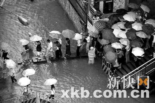 """在岗顶新赛格电子城东侧一处水浸街黑点,广州市自来水公司的工人搭起了""""渡桥""""。"""