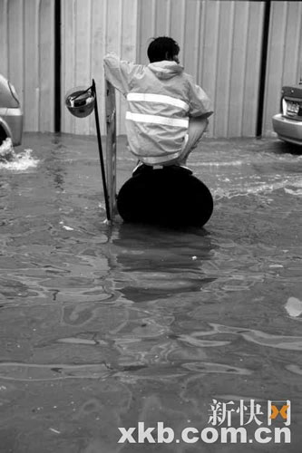 天河路,工作人员打开井盖排水。