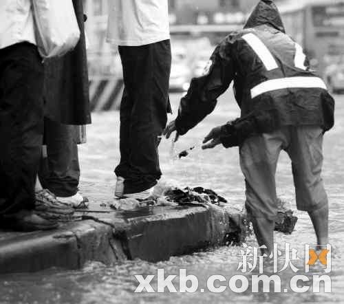 市政工人正把被淹没在水下,堵塞排水口的杂物用手清理到街边。