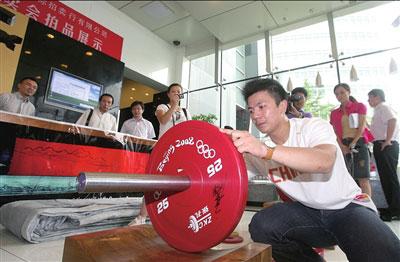 7月27日,在拍品展示现场,张湘祥为赛场上使用过的杠铃签名。本报记者胡雪柏摄