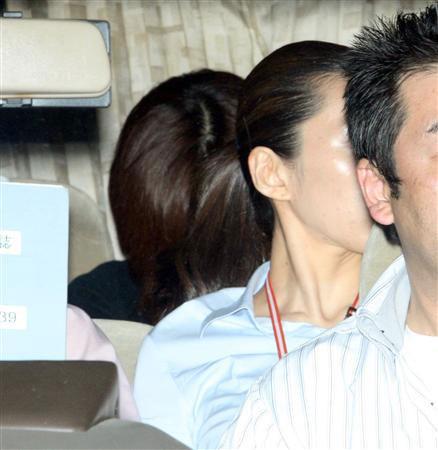 酒井法子乘坐在将她从富坂警察署向涩谷警察署移送的警车后排座位上。她上身著一件极其朴素的衬衫,完全没有了昔日的星之光芒