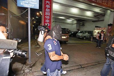 纹身 黑社会/疑为赌档主脑的纹身男子被押走。(图片来源:文汇报)