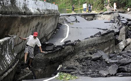 """台南居民走过被台风""""莫拉克""""摧毁的道路。"""