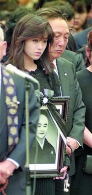 1989年5月,酒井法子怀抱父亲酒井三根城的遗像,出席葬礼