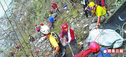 特搜人员以绳索攀爬上陡峭山壁,将罹难飞官遗体吊挂下河谷。