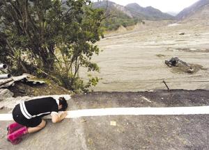 14日,高雄小林村附近的公路上,一名村民悼念在泥石流中丧生的亲人。