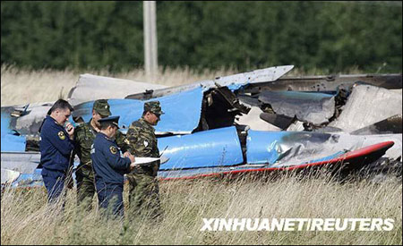 """8月16日,在俄罗斯莫斯科州茹科夫斯基,调查人员在苏-27战机残骸前查看。俄罗斯媒体16日报道,""""俄罗斯勇士""""飞行表演队的两架苏-27歼击机当天在演练时相撞,一名飞行员当场死亡。新华社/路透"""
