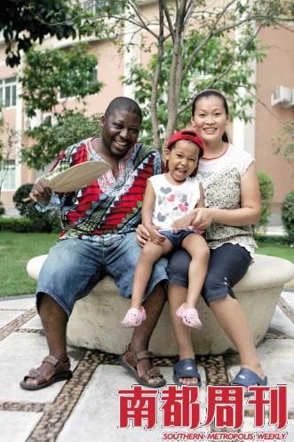 julio和中国妻子及长女在广州租住的公寓楼前合影。