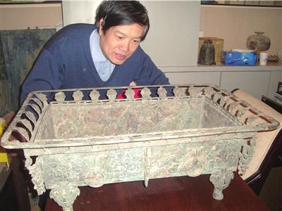 贾文忠正在鉴赏春秋铜盘。供图/贾文忠