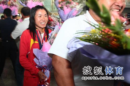 图文:中国田径队凯旋抵京 鲜花丛中一点红