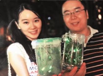 杨帆和女朋友展示自己工厂养殖的萤火虫,杯中的萤火虫星光闪烁。 记者周超摄