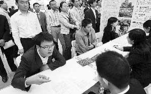 深圳倡导一家企业接收一名大学生。图为大学生在招聘会上求职。(资料图片)本报记者 薛云麾 摄