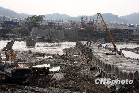 """""""莫拉克""""台风引发的""""88水灾"""",不但造成重大人员伤亡,也导致台湾中南部断桥超过一百座,损失惨重,要完成改建、重建,至少需要数年时间。图为高雄县旗尾大桥(左)几乎全毁,工程人员近日正借助大型机械,加紧搭建一座便桥"""