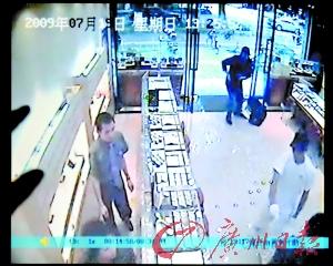 监控录像拍下的劫匪作案图像。