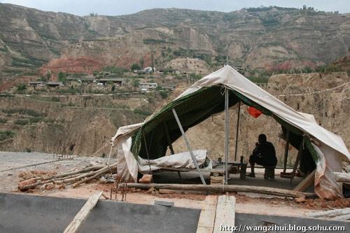 一个灾民在即将竣工的新居屋顶的帐篷里,遥望对面地震中整体摧毁的村庄。这是一个整村新建的居民点,这样的新居民点,陇南有500多个。王子恢摄