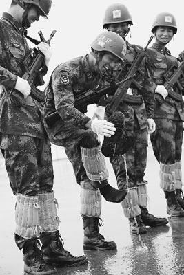 乐观的阅兵队员在雨中训练时,倒出靴子中的积水。