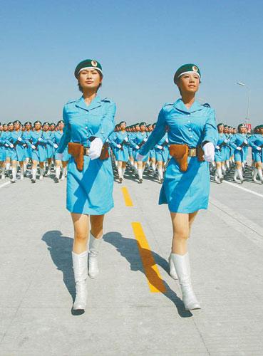"""在北京奥运会上担任颁奖礼仪小姐的张晓菲(左)、赵娜(右)是北京某大学应届毕业生,她俩主动报名参加国庆大阅兵,并在徒步女民兵方队担任领队,完成了从""""猫步""""到正步的转变(7月9日摄)。新华社记者 查春明摄"""
