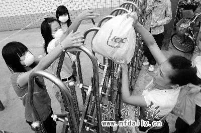 昨日,在西安文理学院门口,家长隔着电动门为学生送生活用品。新华社发