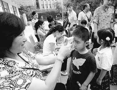 9月7日,南京一所幼儿园的学生在校门口排队测体温入园。尹� 摄(人民图片)