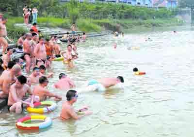 不少南充市民纷纷前往嘉陵江中游泳消暑