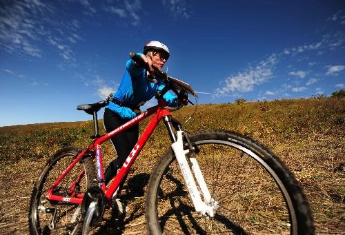 图文:牙克石国际山地车赛 一名选手推车前行