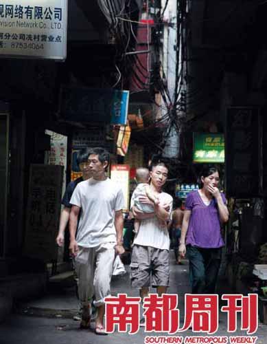 9月7日下午,冼村内握手楼间透下的光线会照射在往来的人群间。 摄影 孙炯