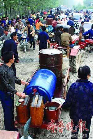 河边的道路挤满了捞油的车辆和村民。