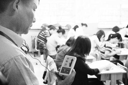 监考老师持防作弊工具巡查考点