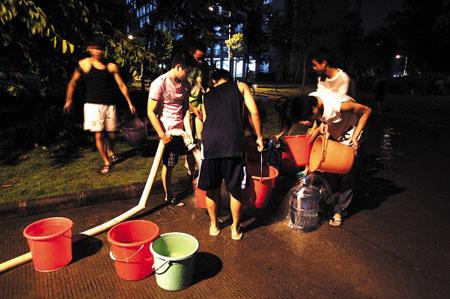 昨晚9时,许多学生借用地下停车场的水管接水 本报记者 陈文笔 摄