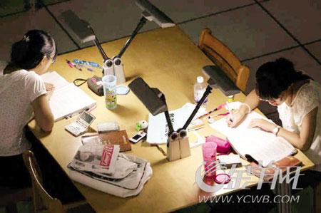 """假期里,忙于""""充电""""的大学生在图书馆奋战 本报记者 侯恕望 通讯员 吴鲁 摄"""