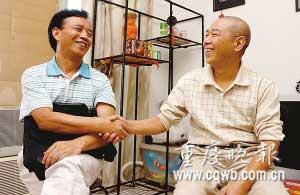 王大爷(右)与被免职的王世明握手,表示接受对方的道歉。 记者 张质 摄