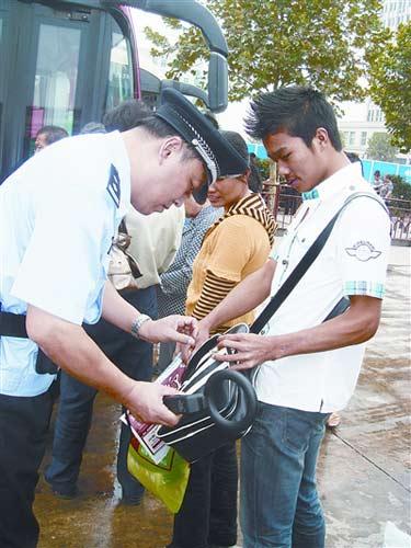 图为民警用金属探测仪对乘客进行安全检查。记者 万勤 摄