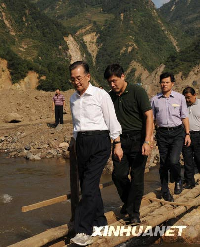 这是9月24日,温家宝在青川县红光乡东河口村踏着由几根枯树杆绑成的独木桥过河看望对岸的村民。新华社记者黄敬文摄