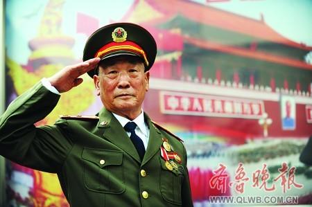 姜志增穿上军装,在一幅天安门画作前敬礼留影。 本报记者 郭建政 摄