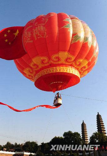 10月4日,为庆贺新中国60华诞,山西太原市双塔寺前升起了一只高14米、宽18米的灯笼形状的热气球,引来不少游人驻足观看。新华社记者 范敏达 摄