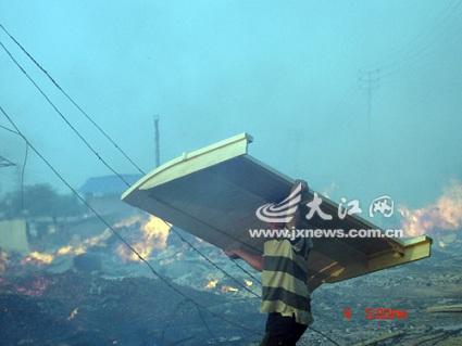 一名工人将加工好的家具从火海里救出
