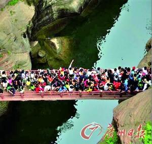 黄金周景点人潮汹涌,游客争过独木桥,问你怕不怕。(资料图片)