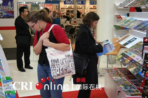 外国友人浏览中国展台,所背的单肩包上充满中国文字(图片来源:国际在线)