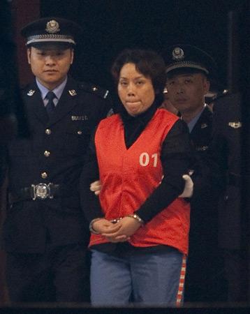 10月15日22时许,谢才萍(中)被押解走出法庭。