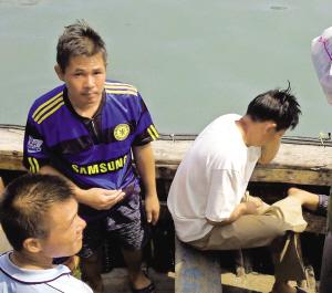获救船员乘坐小船靠岸。本报记者 许海鸥摄