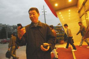 在某建材市场做物管工作的杨远林正在跟儿子杨小强联系 本报记者 石涛 摄