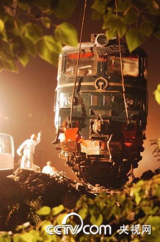 工程人员用吊车把事故机车吊起。(徐彦/CFP)