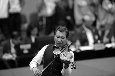 23日,男子56公斤级举重赛场居然出现小提琴演奏,堪称刚柔相济。