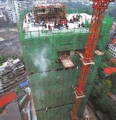 拆迁工人在楼顶拆除违建的几层楼。