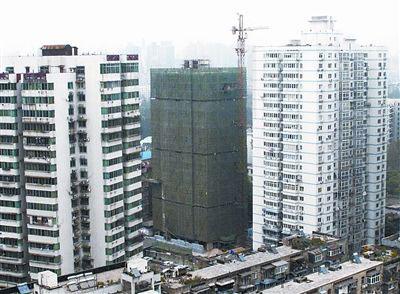 中间为违建加层的施工楼房。