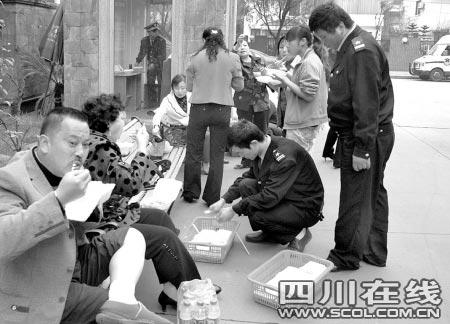 一些留守在小区大门口的业主与原物管的工作人员共进午餐
