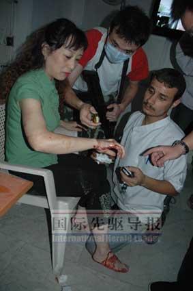 25日,受伤的中国女厨师在大使馆接受紧急包扎。本报记者 高山/摄